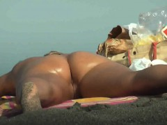 blonde sunbathes nude on the beach and shows a little snatc