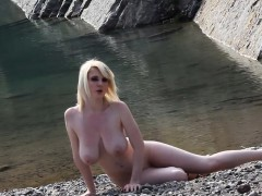 busty-blonde-displays-her-figure-near-the-lake