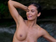 nude-milf-doing-yoga-next-to-a-waterfall